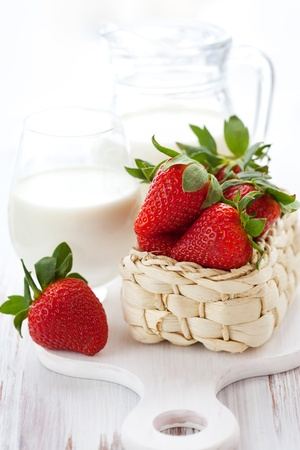 milk jugs: fresh strawberries in a basket and milk in a jug Stock Photo