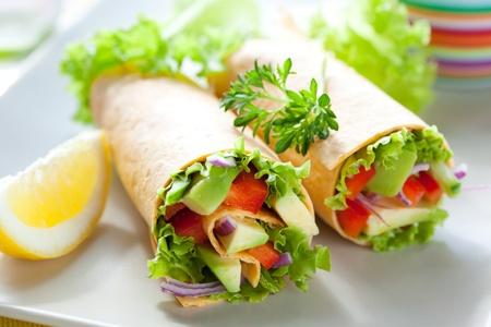 sandwich: tortilla fresca envuelve con vegetales en la placa Foto de archivo