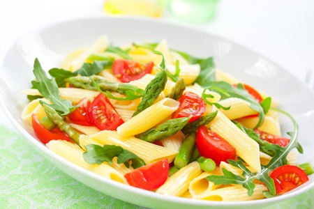 penne: Pasta penne with asparagus,tomato and rucola in bowl Stock Photo