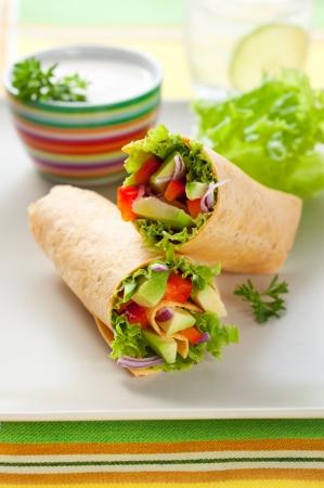 wraps: tortilla fresca envuelve con vegetales en la placa Foto de archivo
