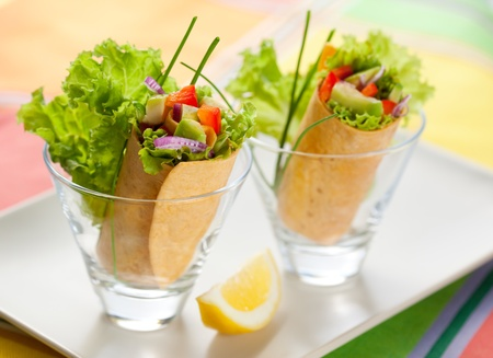 fresh  tortilla wraps with vegetables in glasses photo
