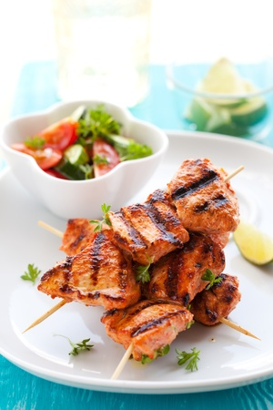 Delicious chicken masala skewers with vegetable salad. photo