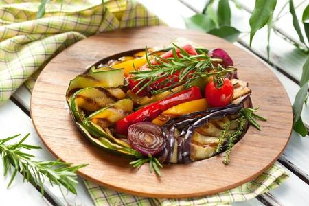 баклажан: Овощи на гриле с розмарином и тимьяном на деревянной тарелке