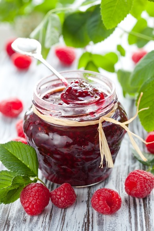 raspberries: raspberry jam in a jar and fresh berries on the wooden table