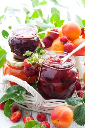 jam: strawberry,apricot, raspberry jam in a jars and fresh berries
