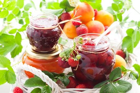 mermelada: mermelada de fresa, albaricoque, frambuesa en una jarras y bayas frescas Foto de archivo