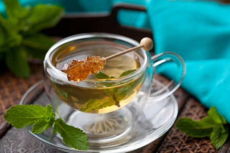 Cup of tea with mint leaves and sugar stir stick photo