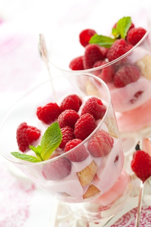 raspberries: raspberry dessert with cream  and biscuits in glasses Stock Photo
