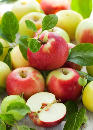 apple red: Red,green and yellow apples with leaves in the basket