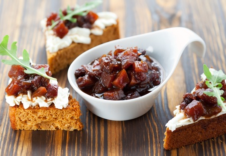 Pumpkin and tomato chutney on pumpkin bread with soft cheese photo