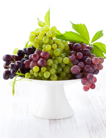 Various types of grapes with leaves on a cake stand photo