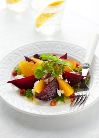 vegetarian food: salad of beetroot,goat cheese,orange and pomegranate