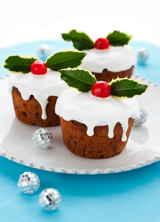 christmas pudding: Christmas mini  cakes with holly leaves and berries Stock Photo