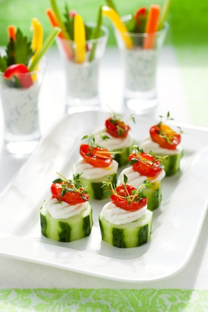 Holiday vegetable appetizers.Cucumbers with soft cheese and sun dried tomatoes and vegetable sticks with dip photo