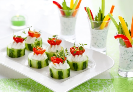 buffet: Vakantie plantaardige appetizers.Cucumbers met zachte kaas en zongedroogde tomaten en groenten sticks met dip