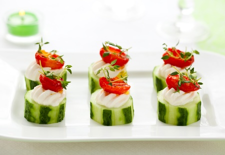 Holiday vegetable appetizers with cucumbers, soft cheese and sun dried tomatoes photo
