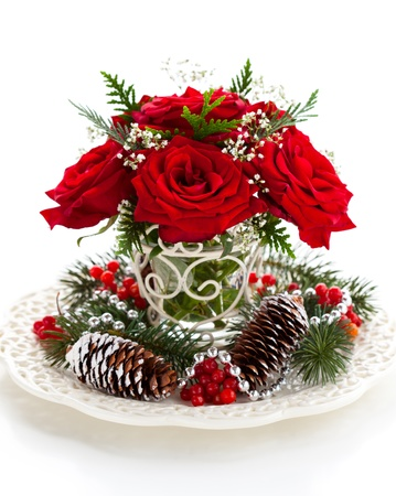 flower arrangement white table: Christmas arrangement of red roses,fir, holly and pine cones Stock Photo