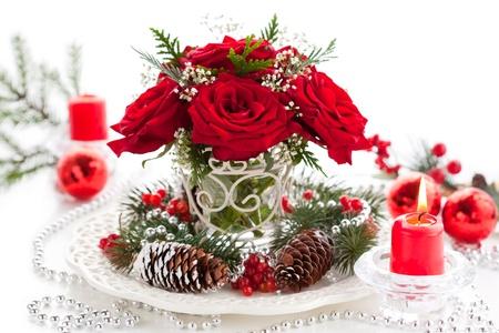 Kerst arrangement van rode rozen, spar, hulst en dennenappels