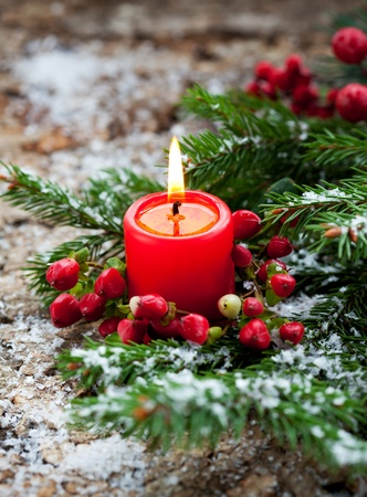 Christmas decoration: fir sprig,candle and berries in snow photo