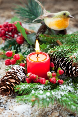Christmas decoration: fir sprig,candle, cones and berries in snow