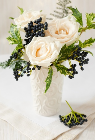 vertical composition: Christmas arrangement of roses,winter berries and holly