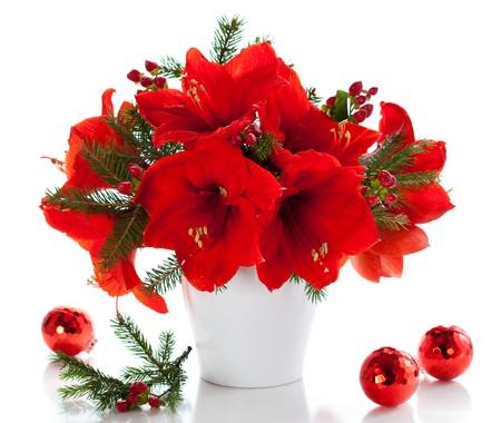 arreglo floral: amarilis rojos en un florero con adornos navideños Foto de archivo