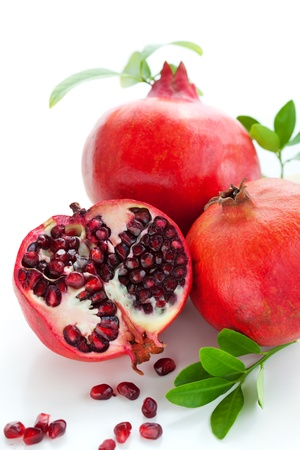 halved  half: Pomegranates, whole and cut open
