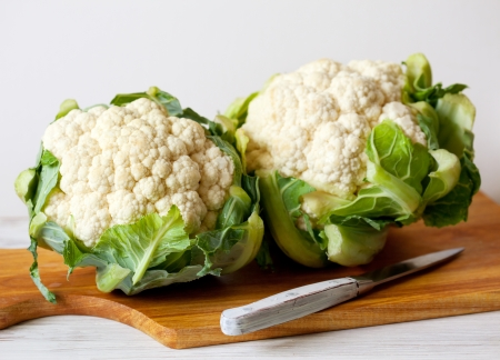 fresh cauliflower with green leaves on cutting board Stock Photo