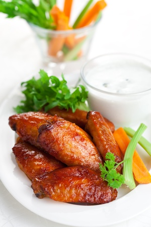 Buffalo chicken wings with blue cheese dressing and  carrot and celery sticks photo