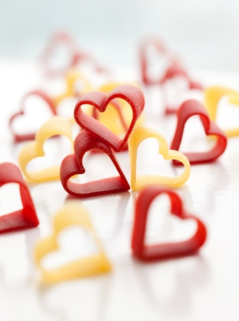 Heart-shaped pasta on the white table photo