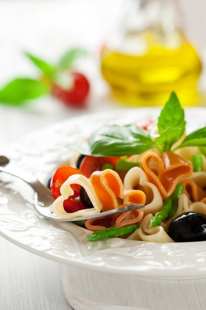 Heart-shaped pasta with tomatoes, asparagus and olives photo