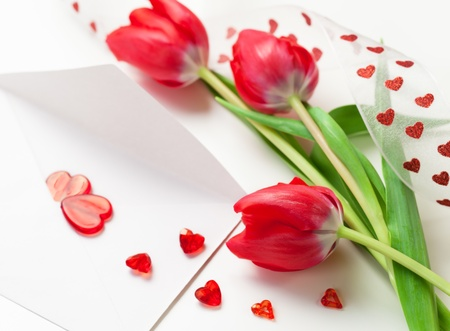 Red hearts on a letter and tulips for Valentines Day
