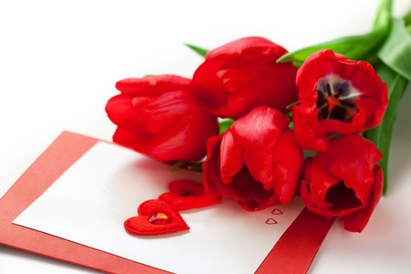 Red tulips and greeting card with hearts for Valentine