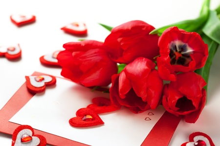 envelope decoration: Red tulips and greeting card with hearts for Valentine