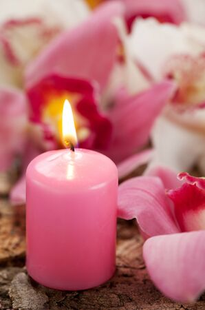 Candle and  orchids on the wooden background photo