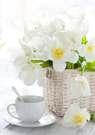 white tulips in a basket and cup of tea on the wooden table photo
