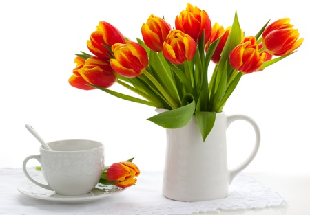 vase: red tulips in a jug and cup of tea on white