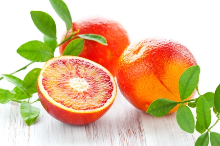 Several blood oranges with leaves,whole and halved on a wooden table photo