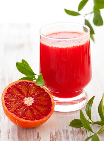 halved  half: blood orange juice in glass with halved blood orange on the wooden table