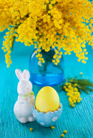 Easter decoration with yellow mimosa and egg photo