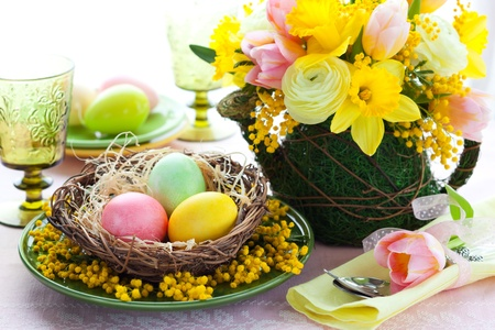 Easter table setting with colored eggs and spring flowers photo