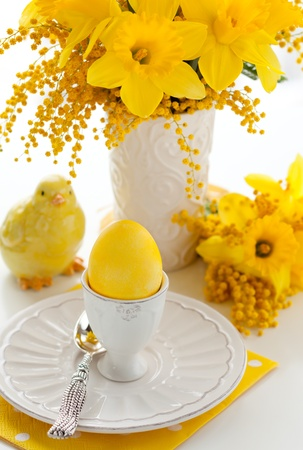 Easter egg in eggcup and bunch of  narcissus and mimosa photo