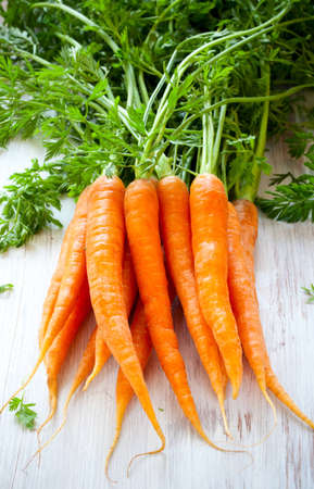 Fresh organic carrots on a wooden table photo