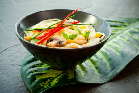 laksa: Bowls of Asian noodle soup with chicken,mushrooms, sweetcorn  and chilli