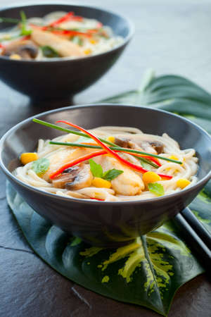 asian noodle: Bowls of Asian noodle soup with chicken,mushrooms, sweetcorn  and chilli