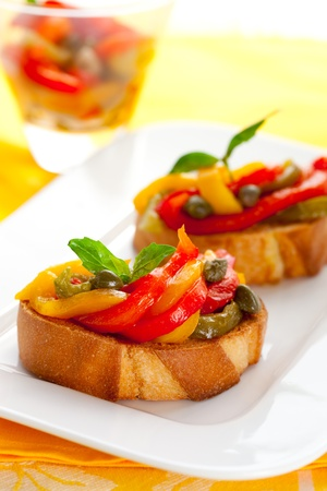 Bruschetta with roasted bell pepper,capers and basil photo
