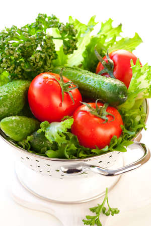 Tomatoes,cucumbers and Lettuce leaves in a colander photo