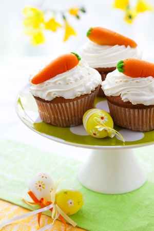Easter  cupcakes with marzipan carrots on a cakestand photo