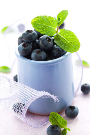 Fresh blueberry in a cup  with leaves of mint photo