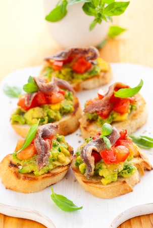 avocado,tomato and anchovy crostini on cutting board photo